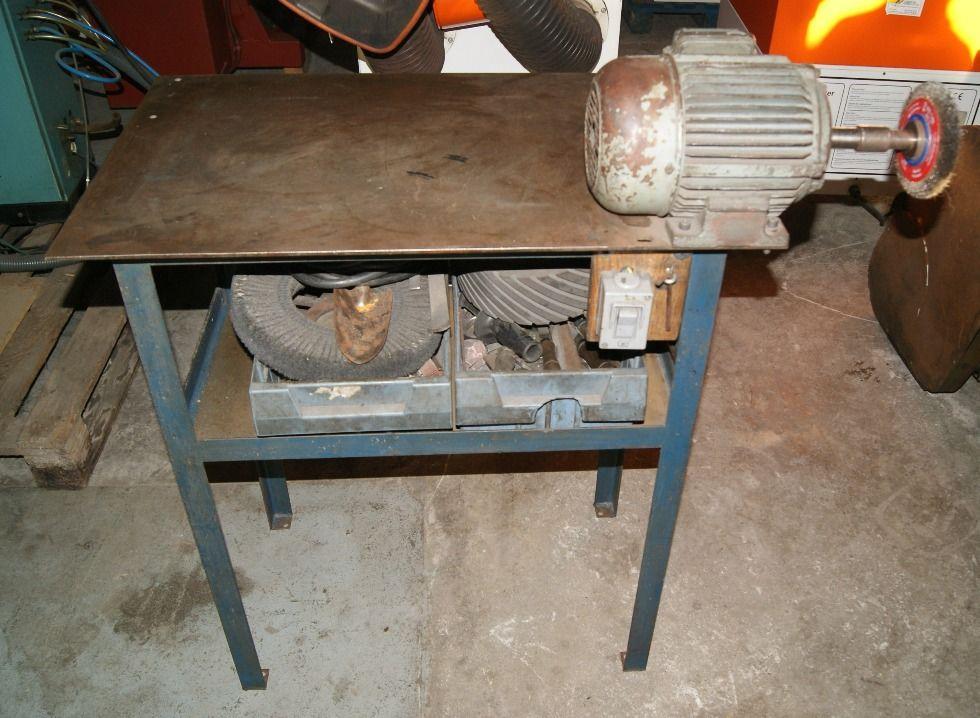 Mesa con esmerilador y varios accesorios.