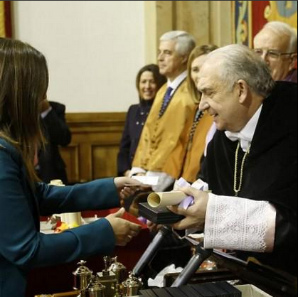 UNA INVESTIGADORA RECOGE SU PREMIO MOSTRANDO SU BILLETE PARA SALIR DE ESPAÑA